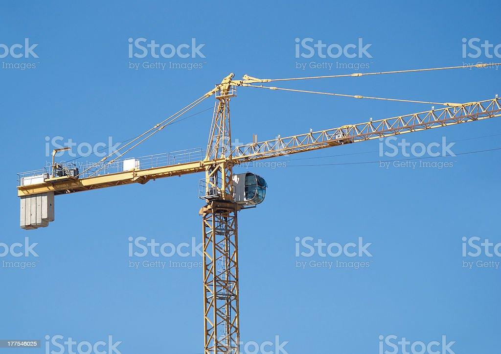 Yellow construction hoisting crane over blue sky royalty-free stock photo