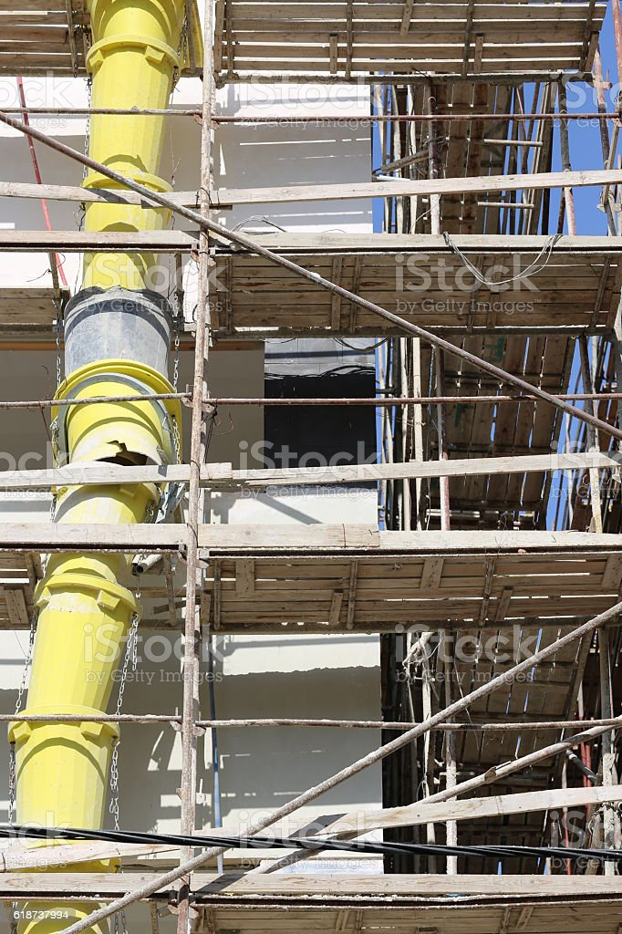Yellow Construction Waste Pipe on a Construction Building. stock photo
