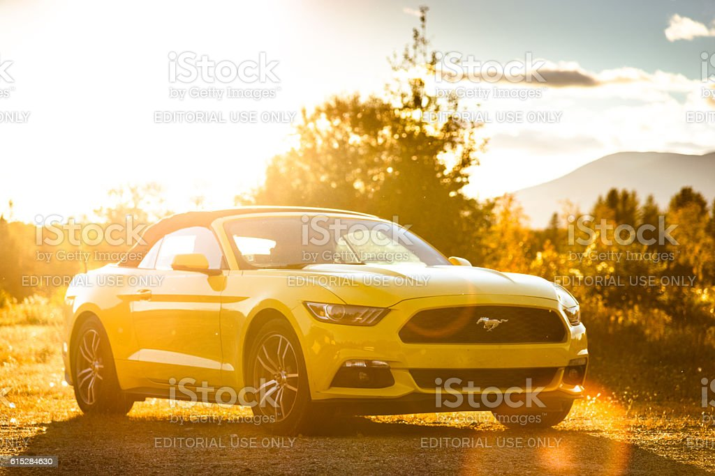 Yellow convertible mustang parked at dusk stock photo
