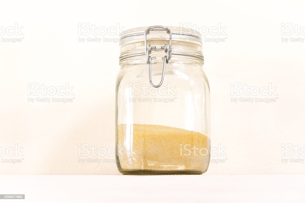 Yellow Cornmeal/Polenta in Mason Jar, White Background, Copy Space stock photo
