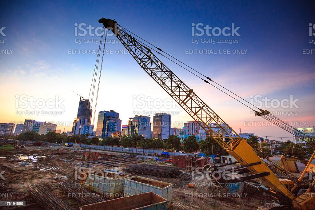 yellow crane on  construction site subway station at sunset stock photo