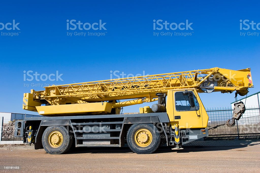 Yellow crane truck against clear blue sky stock photo