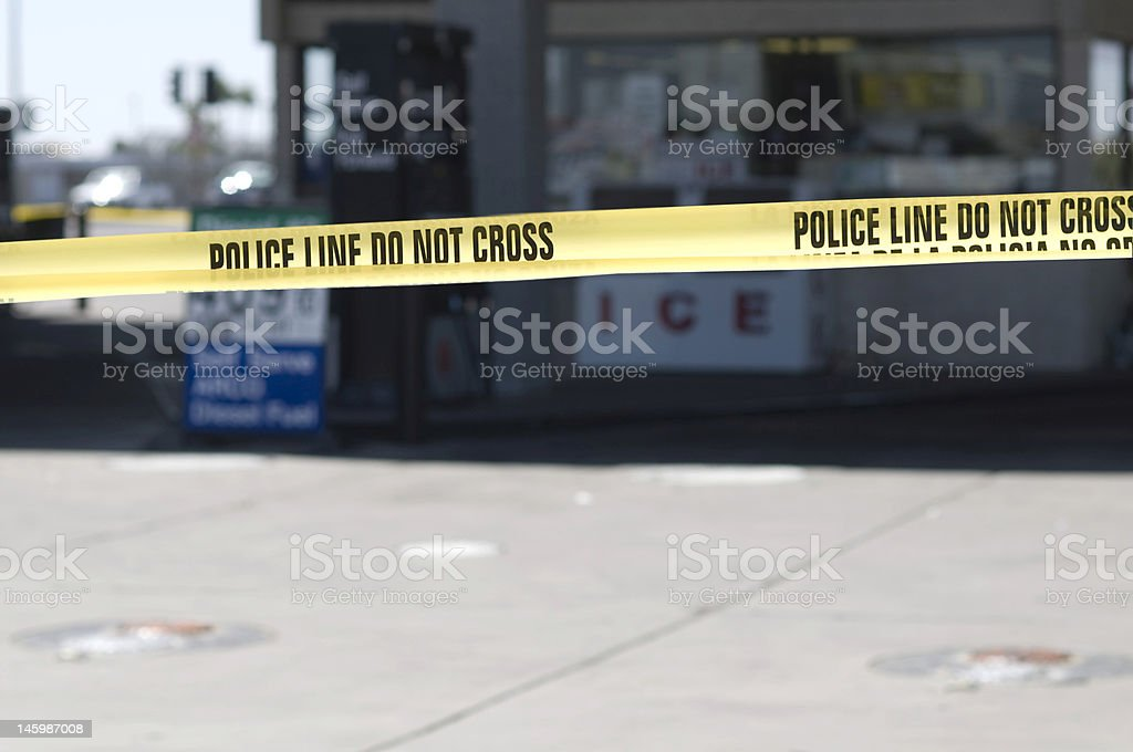 Yellow crime scene tape surronds gas station royalty-free stock photo