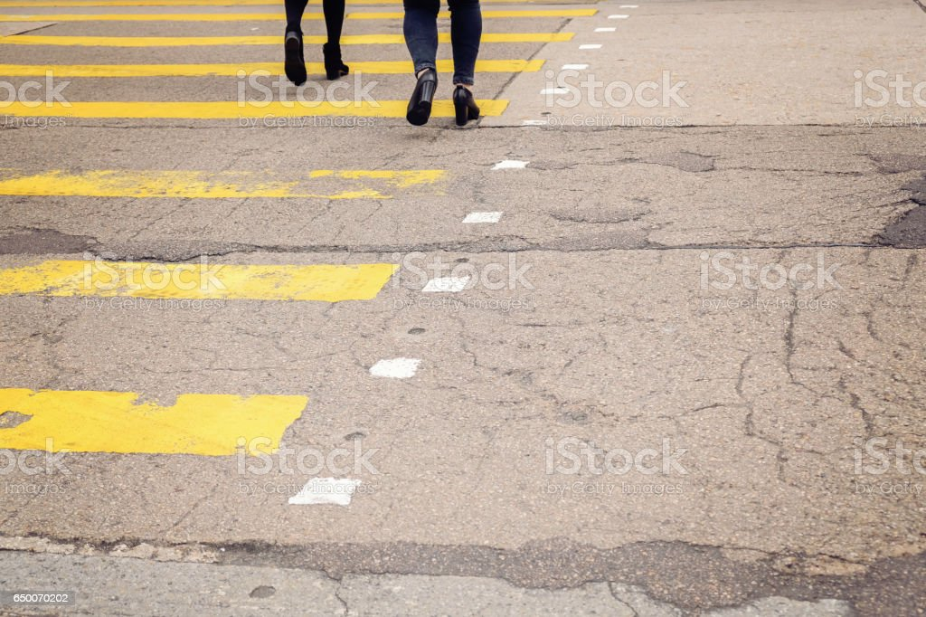 yellow crossroad with walking pedestrians, toning stock photo