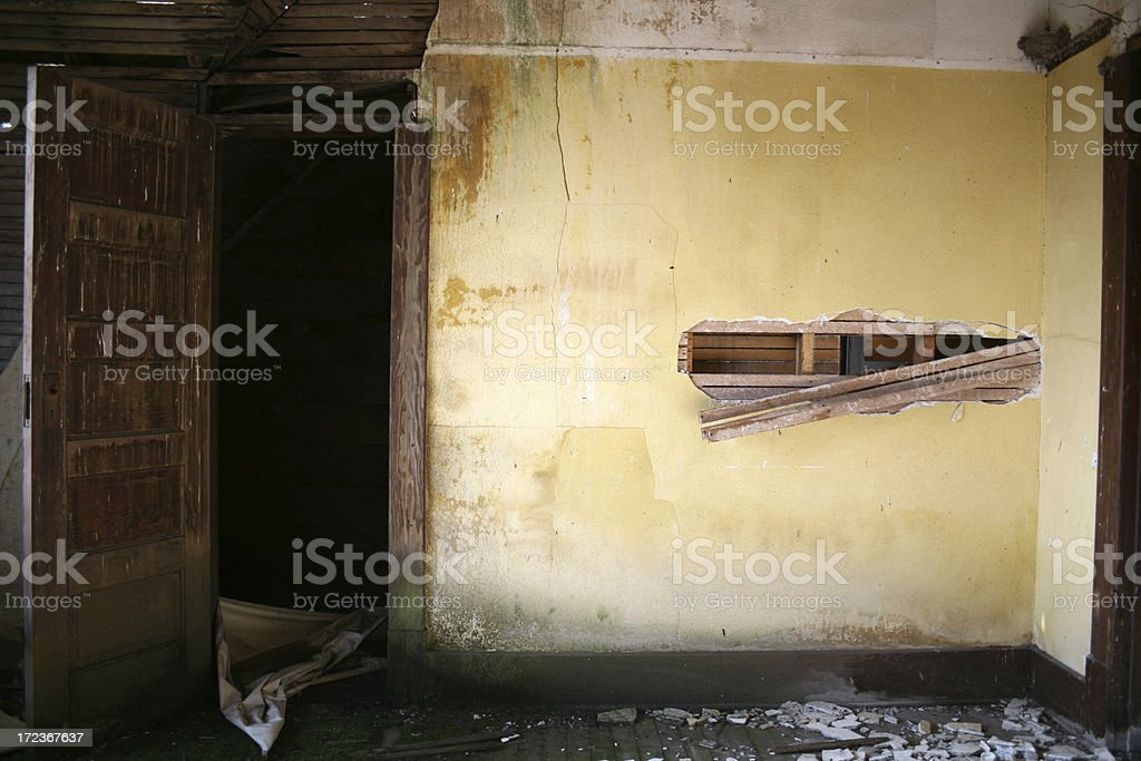 Yellow crumbling water damaged plaster walls, exposed slats and doorway royalty-free stock photo