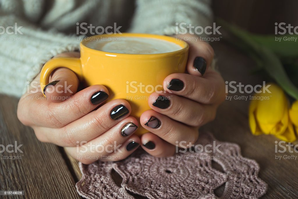 Yellow cup in the hands of women. Gel nail manicures stock photo