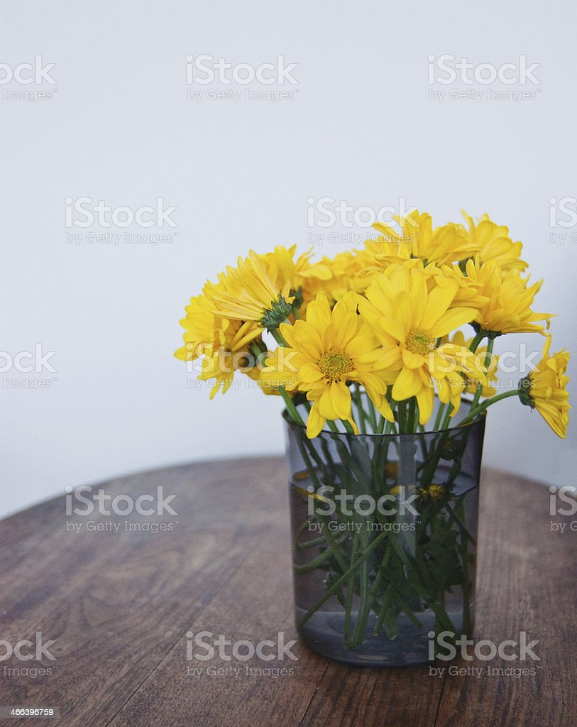 Yellow daisies in glass vase royalty-free stock photo