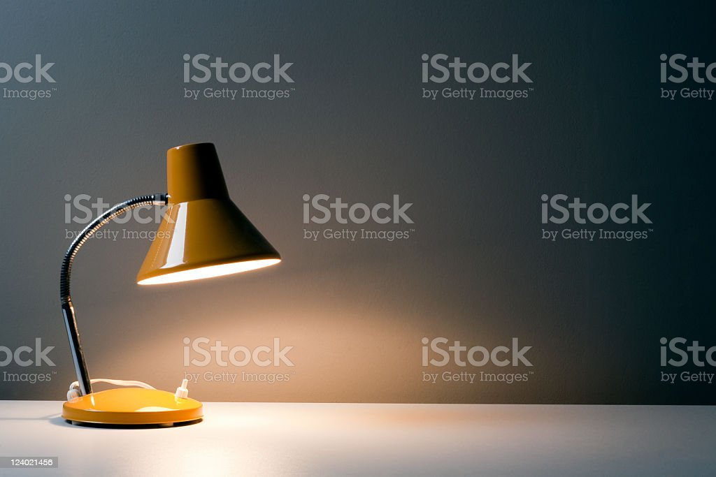 Yellow desk lamp shining light upon a white table stock photo