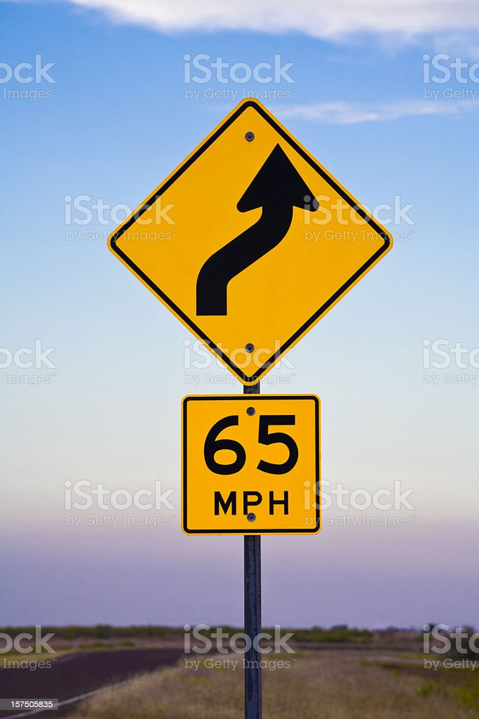 yellow directional road sign 65 mph curve stock photo