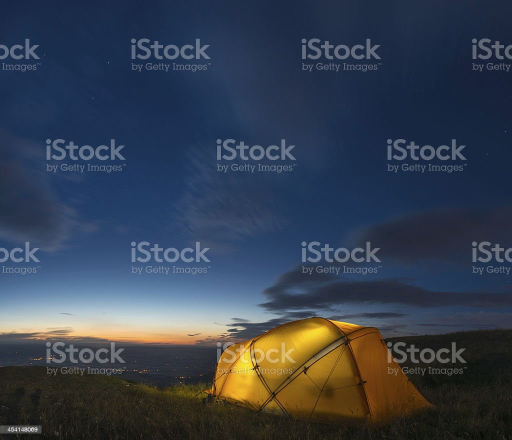 Yellow dome tent illuminated beneath chrome blue starry sky royalty-free stock photo
