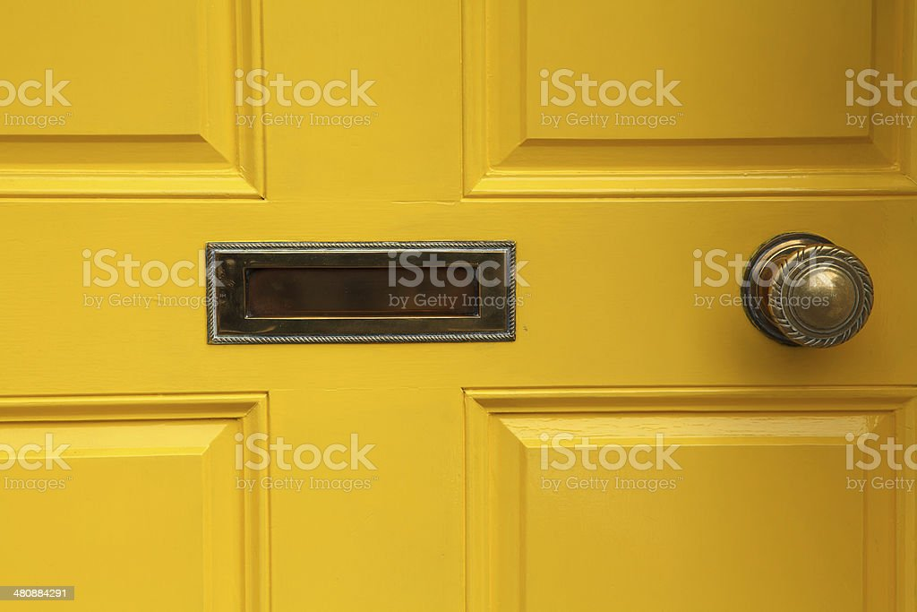 yellow door with letterbox and doorknob royalty-free stock photo
