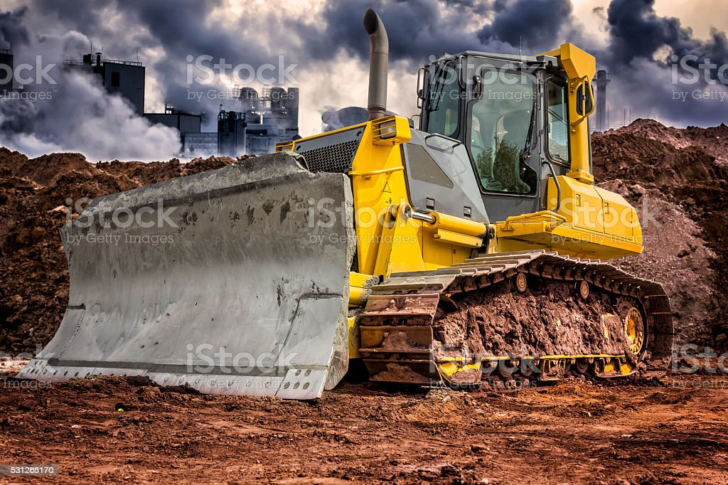 Yellow earth mover in indusrtial zone stock photo