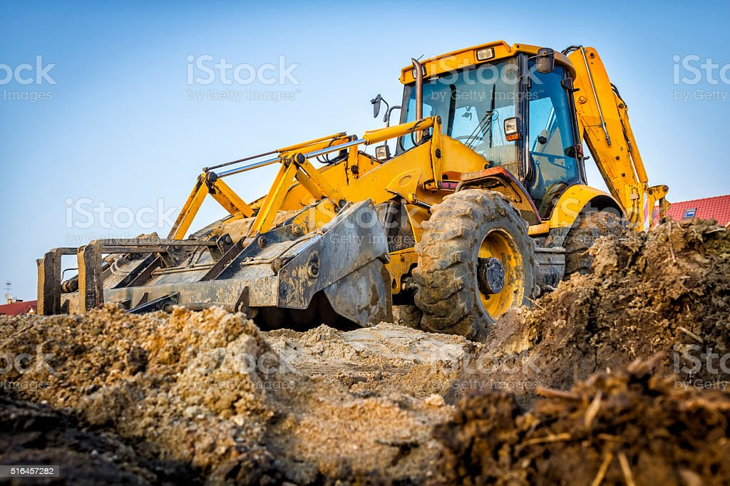 Yellow earth mover on construction site stock photo