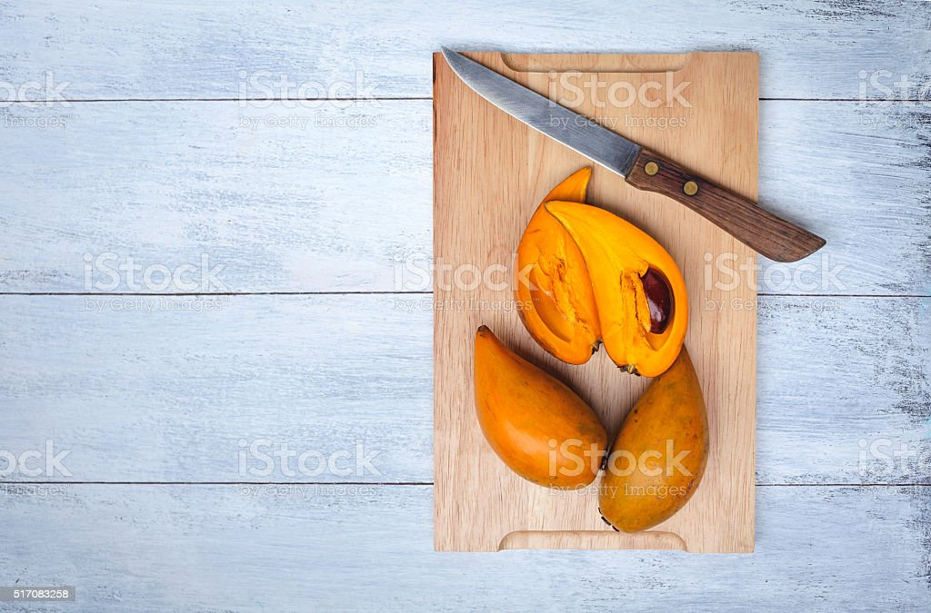 Yellow egg fruit on wood cutting board stock photo