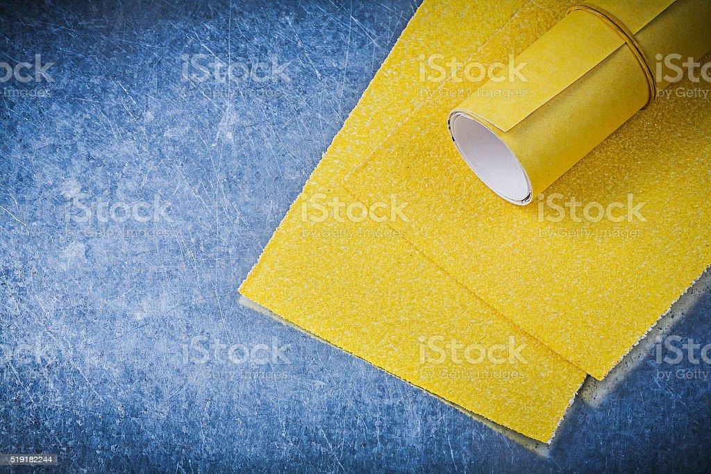 Yellow emery paper on metallic background abrasive tools stock photo