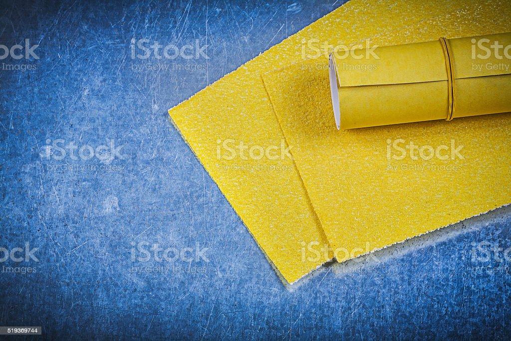 Yellow emery paper on metallic background stock photo