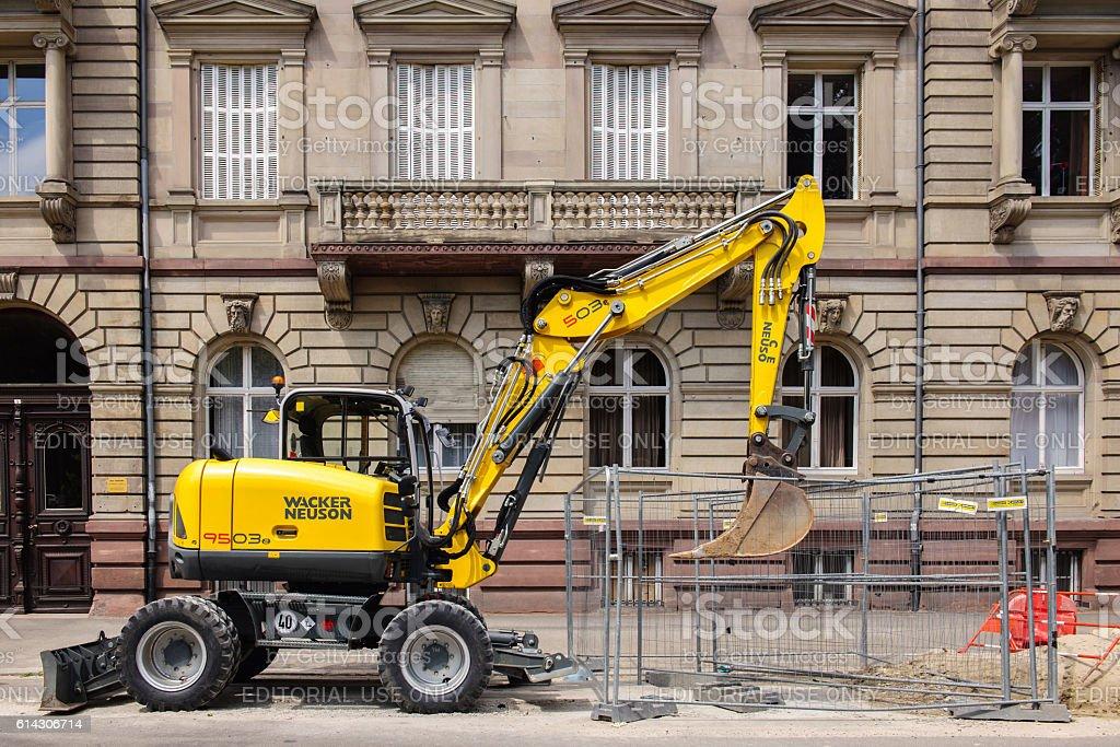 yellow exacavator in urban environment wacker neuson stock photo