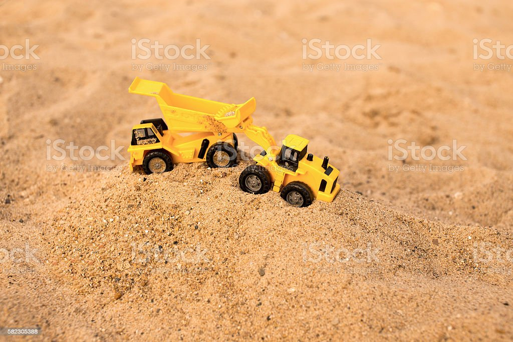 yellow excavator and dumper working in the sand quarry stock photo