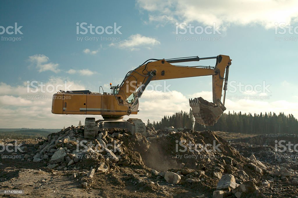 Yellow Excavator Digging a Hole stock photo