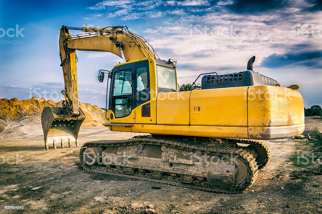 Yellow excavator in a new highway construction stock photo