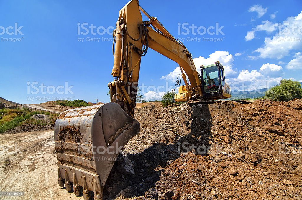 Yellow excavator moving soil and sand on construction site stock photo