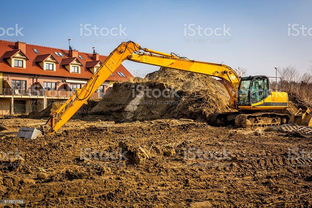 Yellow excavator on construction site stock photo
