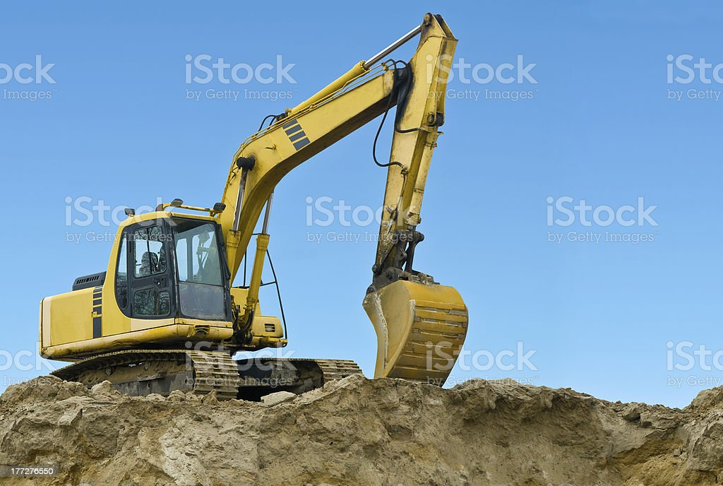 Yellow excavator on sand hill royalty-free stock photo