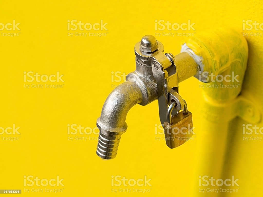 Yellow faucet on yellow wall with padlock prevent water theft stock photo