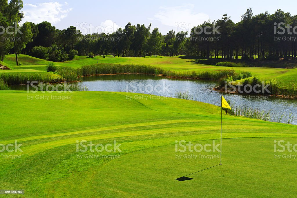 Yellow flag on a lush green golf course with pond stock photo