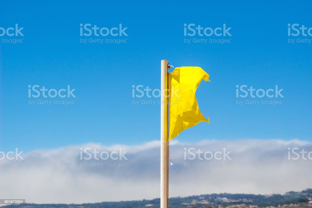 Yellow flag waving in the breeze against a blurred blue sky. stock photo
