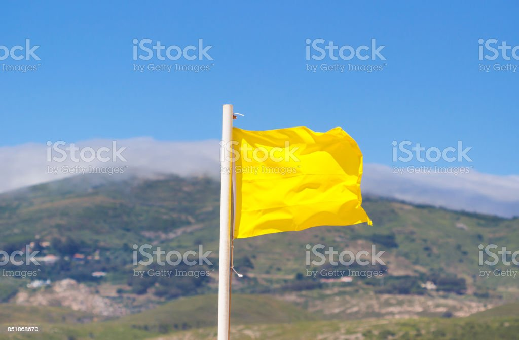 Yellow flag waving on the beach in the breeze against a blurred blue sky. stock photo