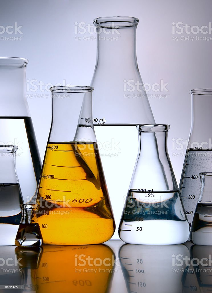 Yellow Flask Amid Group of Erlenmeyers royalty-free stock photo