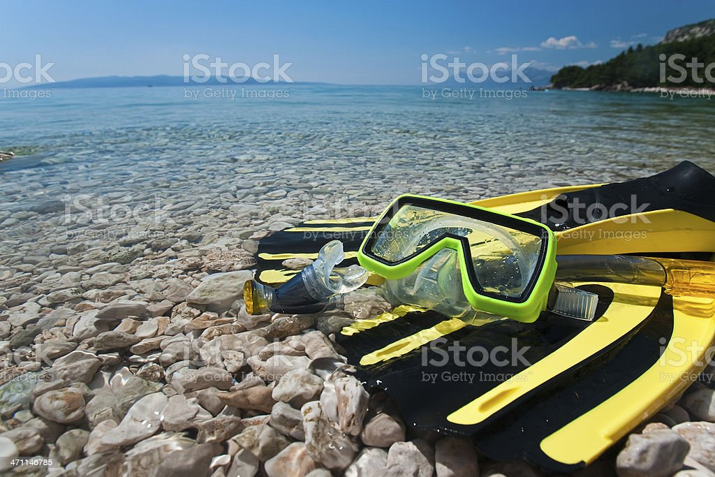 Yellow flippers, mask, snorkel and sea stock photo