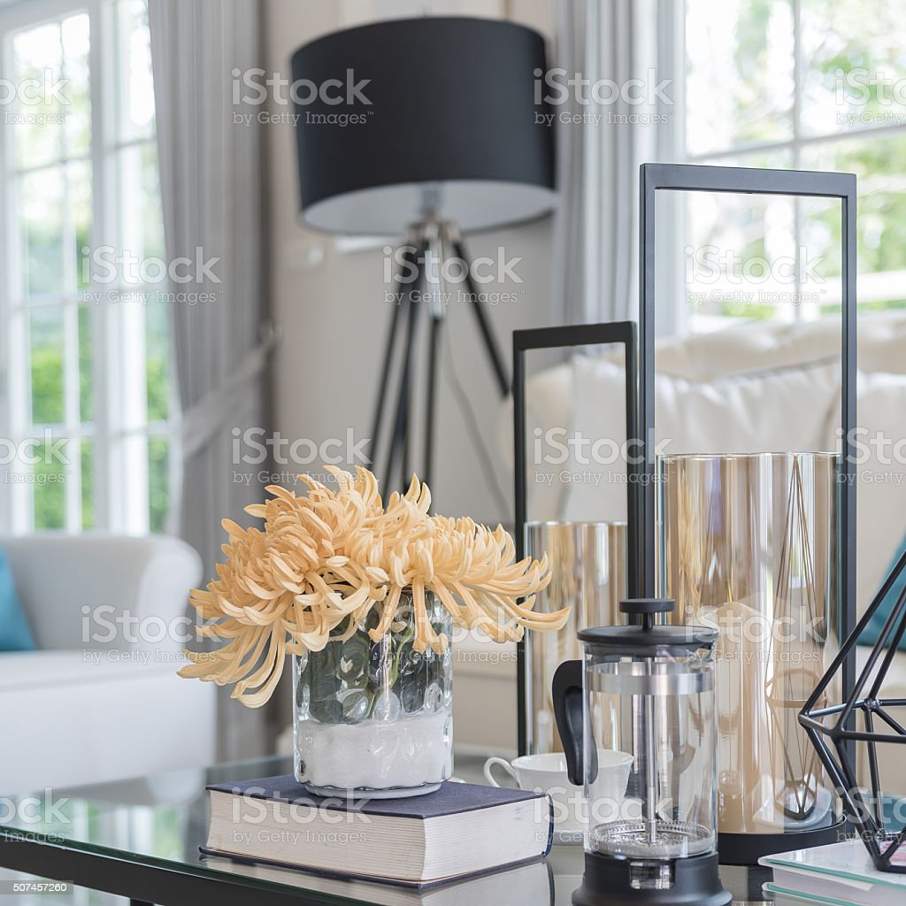 yellow flower in glass vase and book  on glass table stock photo