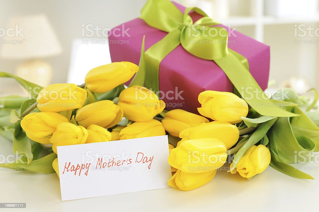 Yellow flowers and a boxed gift with a Mother's Day card royalty-free stock photo
