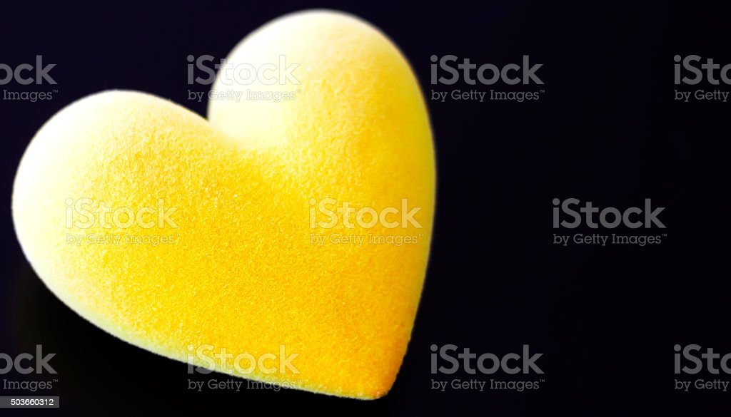 Yellow fluffy heart on a black background stock photo