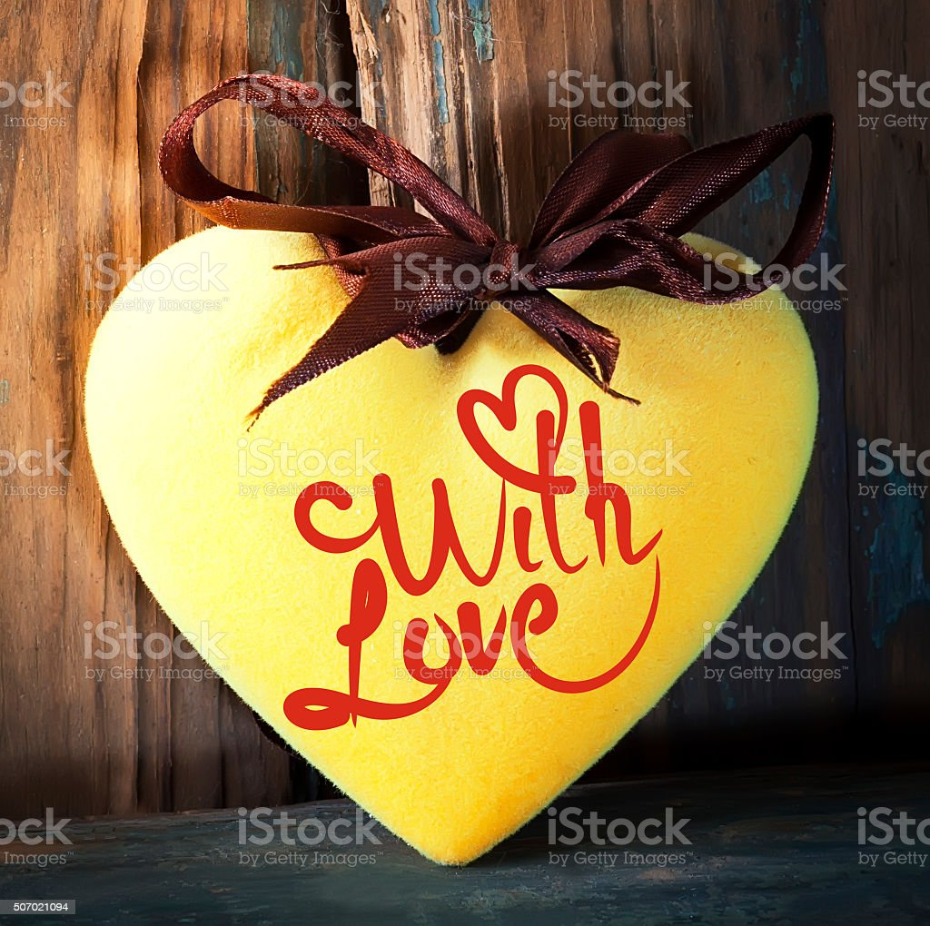 Yellow fluffy heart on wooden texture stock photo