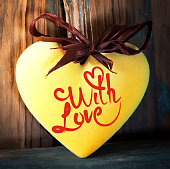Yellow fluffy heart on wooden texture