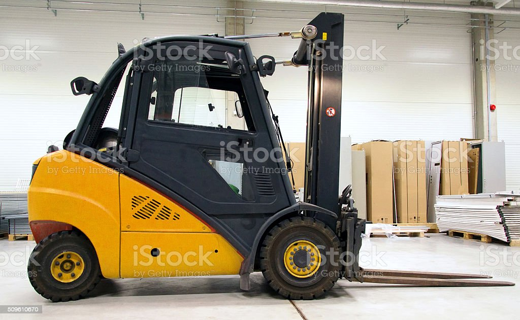 Yellow forklift loader in the large modern warehouse. stock photo