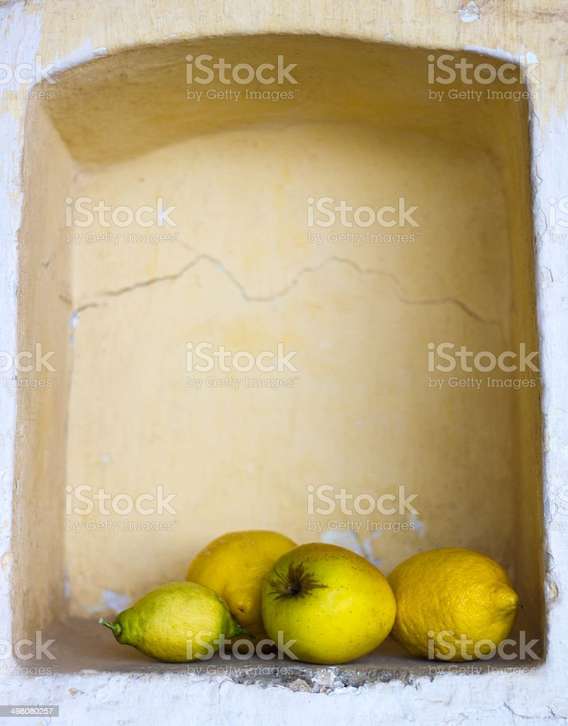 Yellow Fruit in Old Cracked Wall Niche, Italy (Still Life) royalty-free stock photo