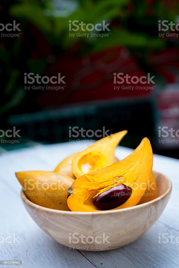 Yellow fruit in wooden bowl stock photo