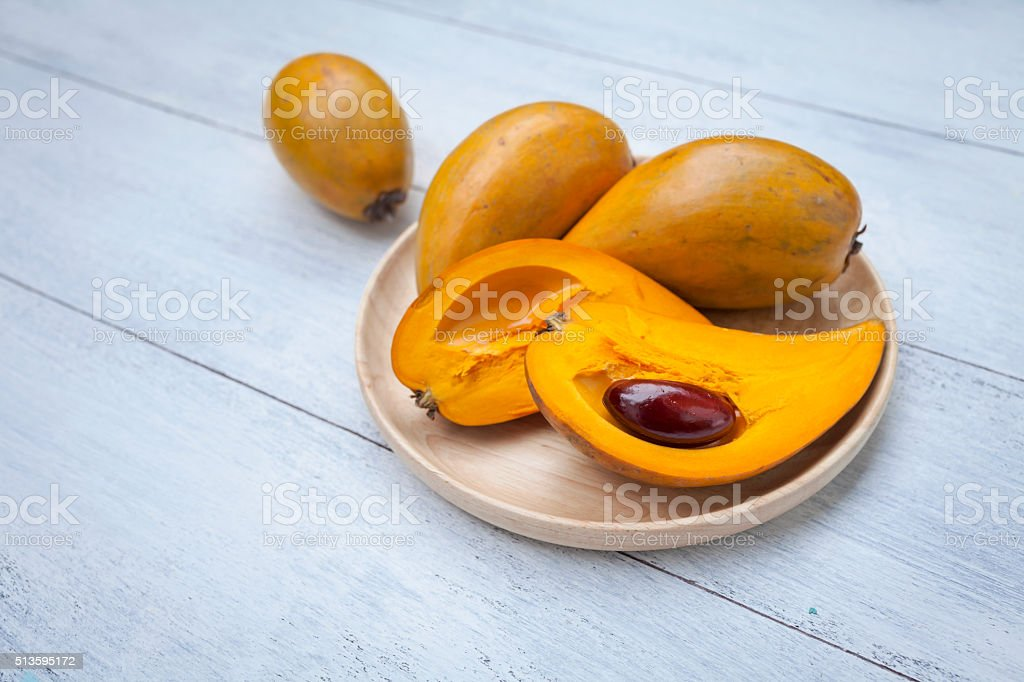 Yellow fruit on wooden tray stock photo