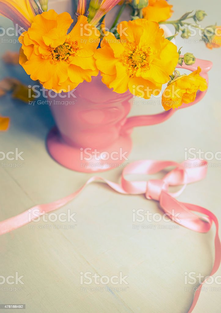 Yellow garden flowers in pink cup and ribbon,  still life stock photo