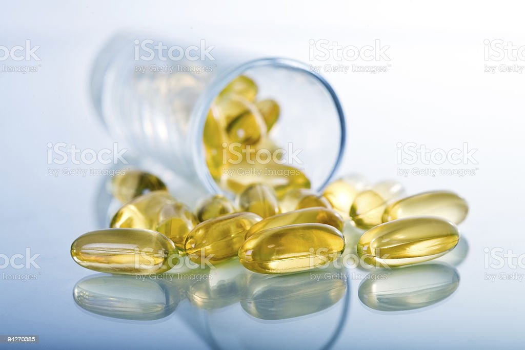 Yellow gel supplements and bottle on gradient background stock photo