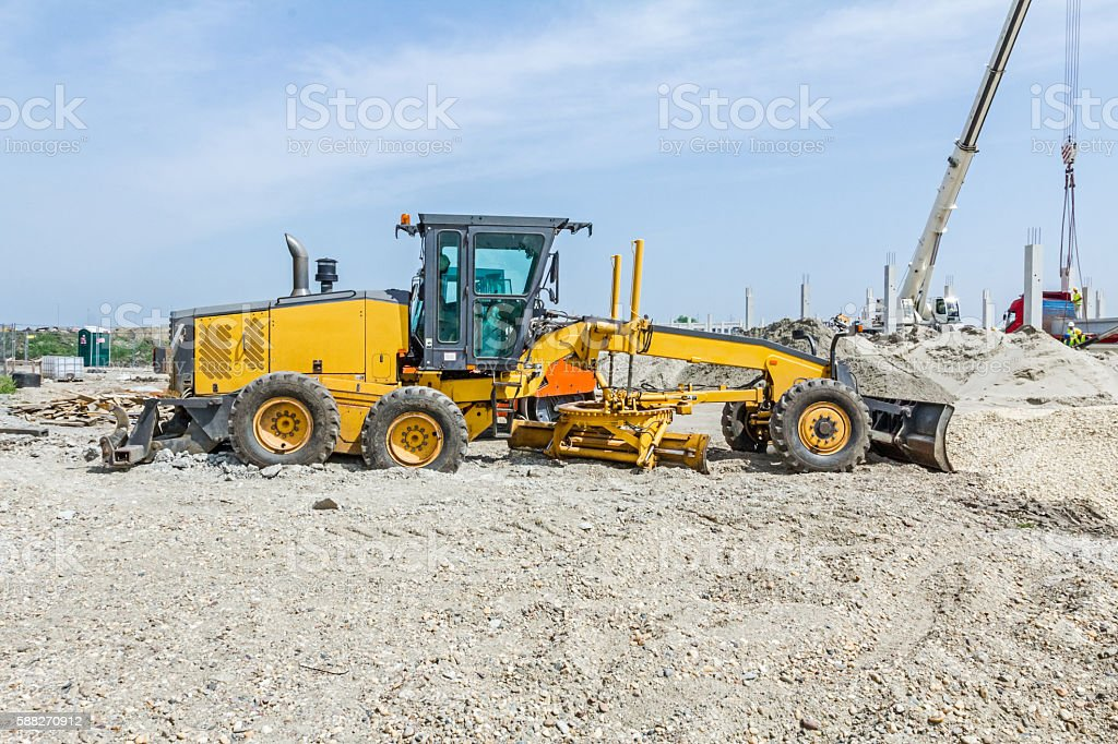 Yellow grader for leveling ground at building site stock photo