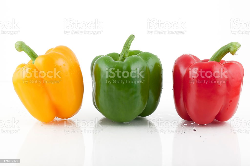 Yellow, green, and red bell peppers on white background stock photo