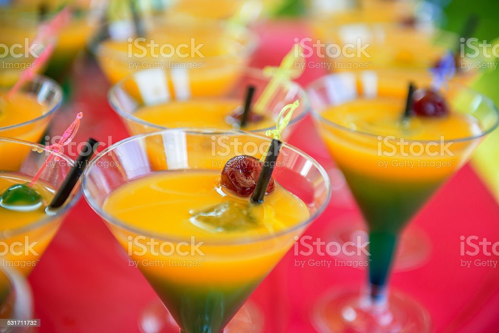 yellow green cocktail with cherry stock photo