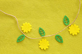 Yellow green textile background from felt with flower and leaves
