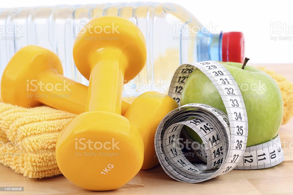 Yellow hand dumbbells, a towel, a measuring tape, an apple royalty-free stock photo