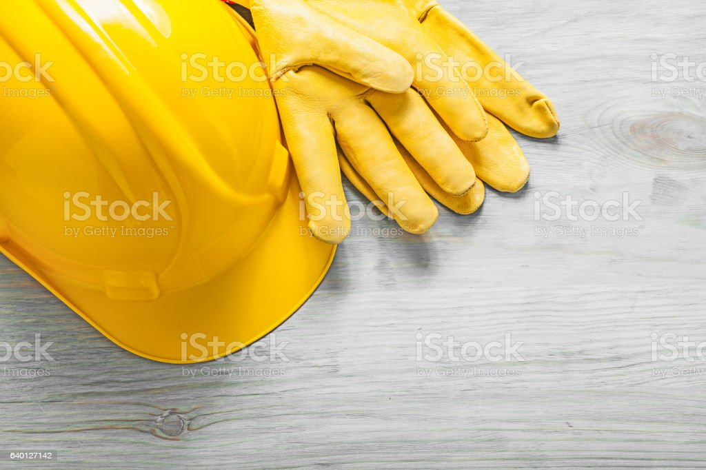 Yellow hard hat leather safety gloves on wooden board constructi stock photo